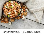 Small photo of Wooden bowl with nuts on a wooden background, near a bag from burlap. Healthy food and snack, organic vegetarian food. Walnut, pistachios, almonds, hazelnuts and nuts of cashew, walnut. Top view. Vert
