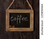 Vintage chalk blackboard on old wood background and coffee beans. - stock photo