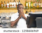 Small photo of Male bartender made a mistake in the bill, emotion. A barmaid registrating new order by cash register. A restaurant worker registrating new order by cash register. The concept of service.