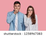 Photo of scared speechless lady and man cover mouthes with palms, have stupefied expressions, dressed in elegant shirt, stand next to each other over pink studio wall. People, reaction and feeling