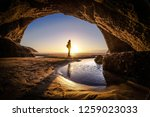 Small photo of Young man stands at a cave exit. A person deep thinking at the exit of a cave. Beautiful landscape formation of a cave in New Zealand