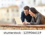 happy couple searching online... | Shutterstock . vector #1259066119