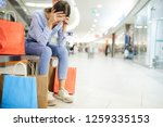 tired shopper holding by head... | Shutterstock . vector #1259335153