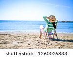 Small photo of relaxed woman in straw hat in chaise longue at the sea watching the blue horizon. peaceful and tranquil mood at sunset
