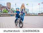 mom teaches son to ride a bike... | Shutterstock . vector #1260060826