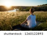 girl meditates sitting on a... | Shutterstock . vector #1260122893