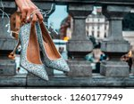 Small photo of A pair of sparkly sequin clad stiletto shoes and fairy lights held by hand