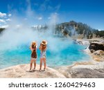 Small photo of Girls relaxing and enjoying beautiful view of gazer on vacation hiking trip. Friends on hiking trip. Excelsior Geyser from the Midway Basin in Yellowstone National Park. Wyoming, USA