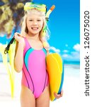 Portrait of the happy girl enjoying at beach.  Schoolchild girl stands  in bright color swimwear with swimming mask on head . - stock photo