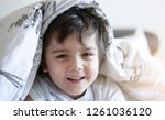 happy adorable boy lying in bed ... | Shutterstock . vector #1261036120