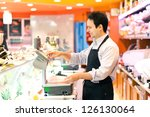 Buthcer in his supermarket - stock photo