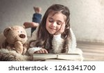 little girl reading a book with ... | Shutterstock . vector #1261341700
