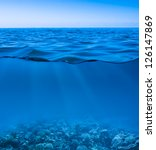 still calm sea water surface with clear sky  and underwater world discovered - stock photo