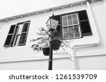 Street lamp with flower pots on house facade in Hamilton, Bermuda. Potted flowers on lighting column with stree lamp. Flower deco. Architecture and street lamp design. Urban streetscape.