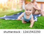 Portrait of cute little caucasian boy having fun in garden with mother. Child crawling on green grass lawn during walk with mom in yard. Happy childhood and baby healthcare.