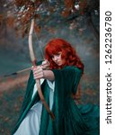 red haired girl holds a bow in... | Shutterstock . vector #1262236780