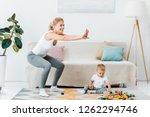 attractive mother doing squats... | Shutterstock . vector #1262294746