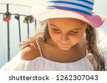 little girl in a hat on summer... | Shutterstock . vector #1262307043