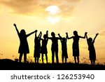 Group of happy children standing on meadow at summer sunset - stock photo