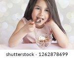 happy child girl eating ice...   Shutterstock . vector #1262878699