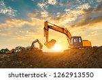 Three Excavators Work On...