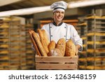 baker holding a basket full of... | Shutterstock . vector #1263448159