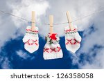 hat and pair of gloves drying in the open air hanging on clothes line affixed with wooden pegs - stock photo