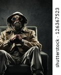 Man In Gas Mask Sitting In A...