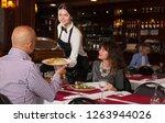 young waitress bringing... | Shutterstock . vector #1263944026