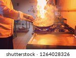 chef cooking and doing flambe... | Shutterstock . vector #1264028326