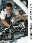 Small photo of Serious man fixing breakage in hood of automobile at car service. Slilled mechanic in white shirt, grey uniform and protective gloves repairing broken vehicle. Concept of maintenance.