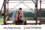 Person working in construction site. White young man at work in new house, smiling and using smartphone for internet and social media during break - stock photo