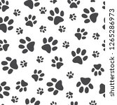 Stock vector vector illustration animal paw track seamless pattern backdrop with monochrome silhouettes of cat 1265286973