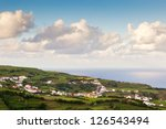 View to small town near atlantic ocean under heavy clouds, Azores, Portugal - stock photo