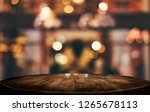 Stock photo selective empty wooden table in front of abstract blurred festive light background with light spots 1265678113