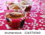 Freshly baked muffins made with carrots and almonds in red paper cups on white and red background - stock photo