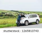 man stand near broken car with... | Shutterstock . vector #1265813743