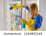 young woman in yellow gloves... | Shutterstock . vector #1265892169