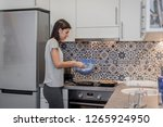 young woman in kitchen making... | Shutterstock . vector #1265924950