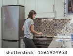 young woman in kitchen making... | Shutterstock . vector #1265924953