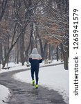 man jogging in a cold winter... | Shutterstock . vector #1265941579