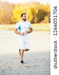 Small photo of Fitness. Stretch man doing stretching exercise. Standing forward bend stretches of legs.