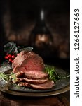 Small photo of Succulent prime roast beef topside rump joint carved and ready for serving. Shot against a rustic, festive background with generous accommodation for copy space.