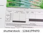 Receipt Russian language for payment of the used water and some of the new banknotes of 200 rubles. Calculation of utilities - stock photo