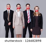 Small photo of Businesspeople bound by red tape around their mouths standing in a row unable to speak or divulge information