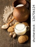 oatmeal cookies and jug of milk on old wooden table - stock photo