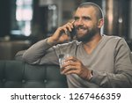 smiling man talking by phone in ... | Shutterstock . vector #1267466359