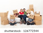 Happy family with four kids in their new home - among cardboard boxes - stock photo