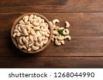 Tasty cashew nuts in bowl on wooden table, top view. Space for text