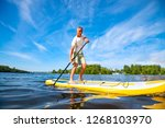 happy man is paddling on a sup... | Shutterstock . vector #1268103970